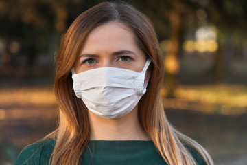 Young woman wearing white cotton virus mouth nose mask, nice bokeh - blurred park trees - in...