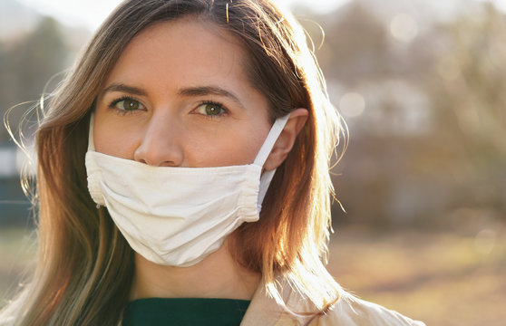 Young woman wears home made white cotton virus mouth face mask, wrong way, incorrect wearing - masks should cover nose as well