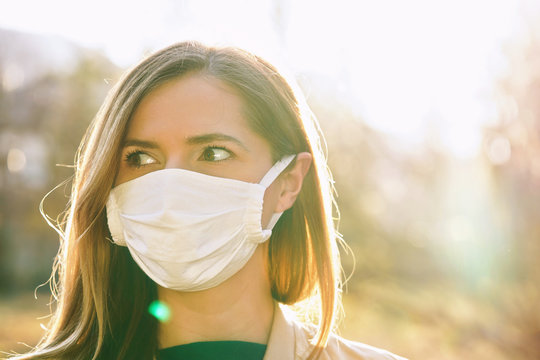 Young woman wearing white cotton virus mouth nose mask, nice backlight sun bokeh in background, closeup face portrait