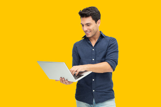 Portrait of an excited man holding laptop computer isolated on yellow background, Feeling happiness, Caucasian Male model