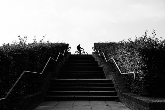 Low Angle View Of Steps Leading Towards Man With Bicycle On Road
