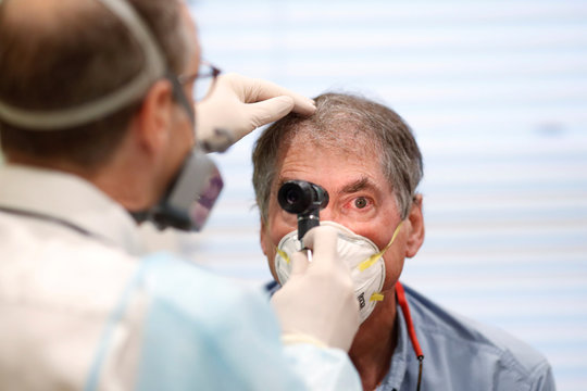 Dr Greg Gulbransen performs a medical checkup on a 72-year-old man with Leukemia who is presumed to have the coronavirus disease (COVID-19) while working in an isolated room at his pediatric practice in Oyster Bay, New York