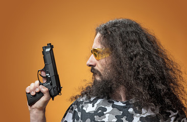 Portrait of a skinny man poiting a gun - isolated
