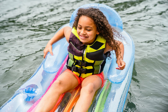 Smiling girl in life jacket playing on inflatable floaty on lake in summer