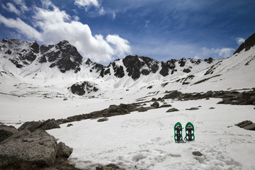 Fototapete - Pair of green snowshoes in snow. High snowy mountains and blue sky