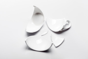 broken white ceramic tea cup on a white background, conceptual photo with a shattered object.