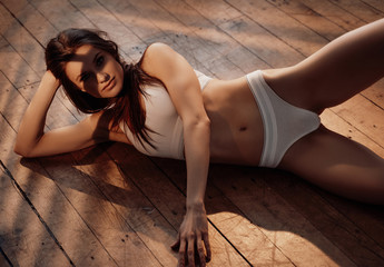 Photo of a half-nude beautiful female model posing while relaxing on a wooden floor, wearing sporty underwear, looking smooth and sensual