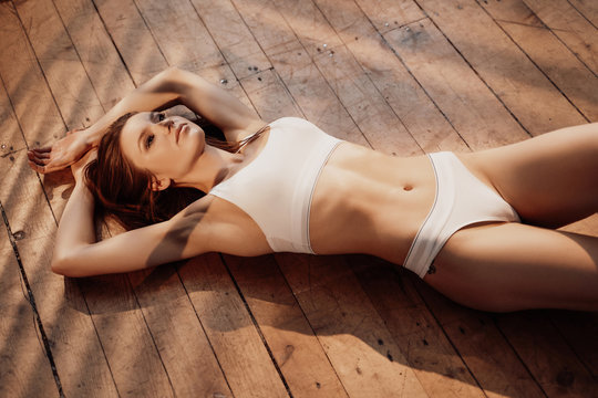 Hot and seductive young female model with dark hair and sporty underwear posing while laying on a wooden floor in a bright room filled with sunlight, looking daring and erotic