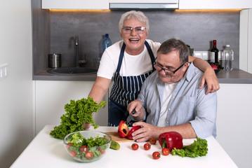 Senior couple chopping salad together. Elderly people staying home during coronavirus quarantine.