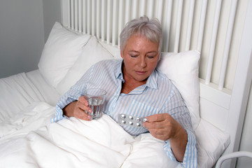 Elderly woman laying in bed. Going to take her pills. Holding glass of water.