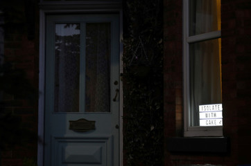 "An illuminated sign saying 'Isolate with cake"" is seen in the window of a house, as the spread of the coronavirus disease (COVID-19) continues, Manchester, Britain"