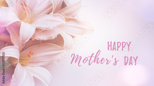 Happy Mother's Day card with beautiful pink lily flowers in a gift box flat lay on pastel table top, spring card, top view. Spring or summer card with flowers, top view, copy space