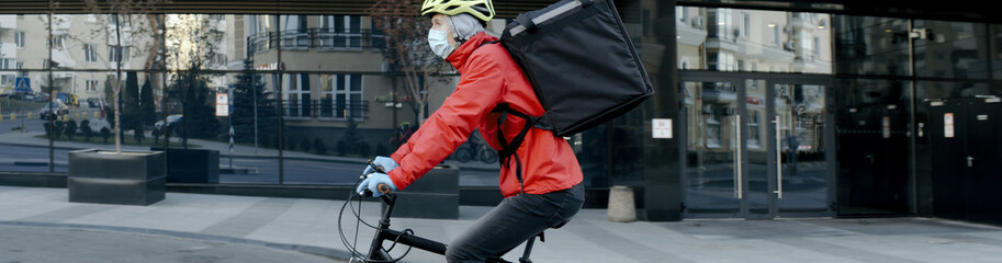 Courier wearing medical mask and gloves riding a bicycle to deliver food order to customers during virus outbreak. Coronavirus, COVID-19, safe delivery Fototapete