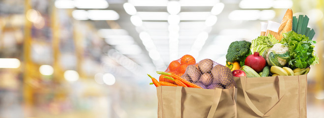 Eco friendly reusable shopping bags filled with bread, fruits and vegetables on a supermarket background