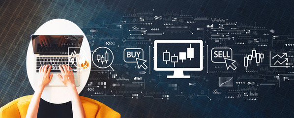 Wall Mural - Stock trading theme with person using a laptop on a white table