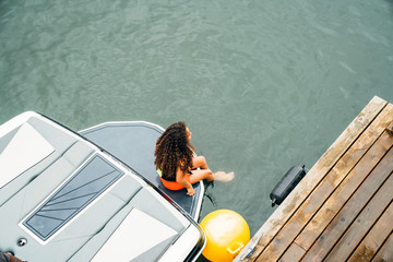 Girl in life jacket sitting on boat next to dock on lake with feet in water Fotomurales