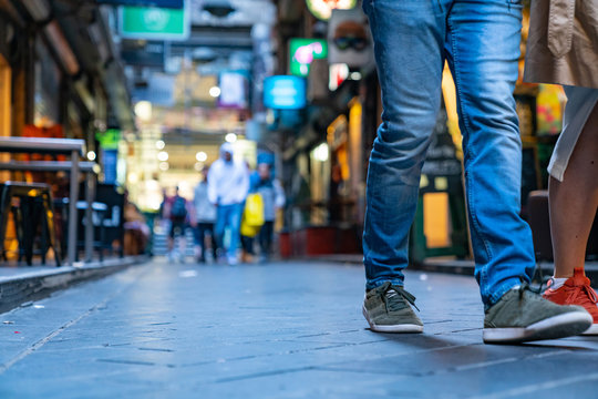 People in Degraves Street Melbourne, all unrecognisable and defocused except close legs walking by, all branding removed.