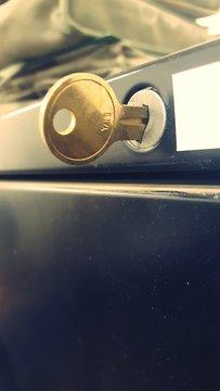 Close-up Of Gold Key In Lock On Metallic Drawer