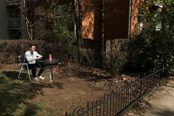 Noah Allentoff works on a laptop in his front yard, following Governor Ralph Northam's declaration of a state of emergency due to the coronavirus disease (COVID-19) in Arlington, Virginia