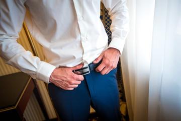 Fototapeta A stylish man puts on a leather belt close-up. Fashion
