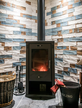 Modern wood burning stove. Tiled wall behind, stove with fire burning inside, cosy and warm interior scene, heating in winter.