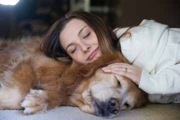 Teenage girl sleeping on the floor next to her golden retriever dog