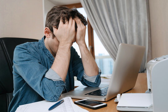 Tired stressed young man sitting in front of laptop, frustrated with problems or study failure, feel exhausted, having headache, upset with bad news, money problem, unsuccessful exam or test results