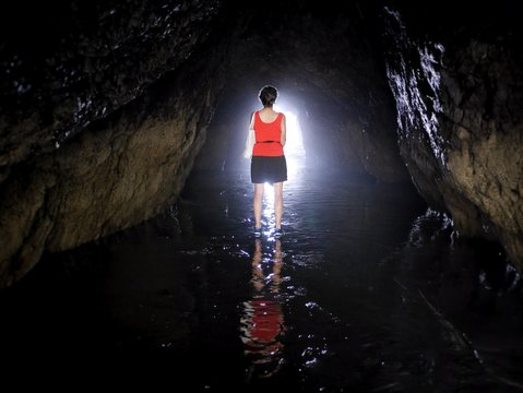 Rear View Of Woman Standing On Water In Cave