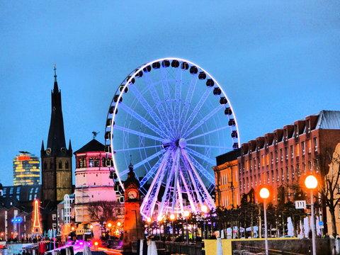 Illuminated Ferris Wheel By Church In City Against Sky At Dusk