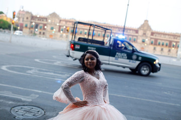 A girl poses for her quinceanera pictures in Zocalo Square amid the outbreak of the coronavirus disease (COVID-19), in Mexico City
