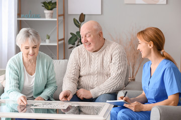 Elderly people suffering from mental disability and caregiver in nursing home Wall mural