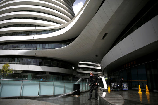 Worker wearing a face mask cleans floors at the Galaxy Soho office buildings in Beijing