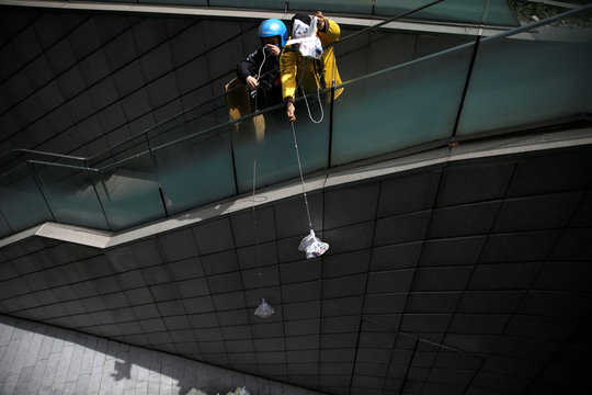 Delivery workers pull ropes to pick up food from restaurants as the nearest entrance to downstairs has been blocked following the novel coronavirus disease (COVID-19) outbreak, in Beijing