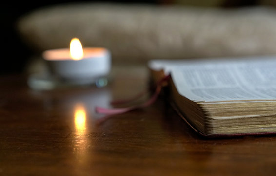 Open bible with burning candle on the table
