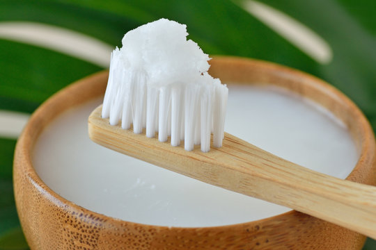Coconut oil in a bowl with a wooden toothbrush - Homemade whitening toothpaste