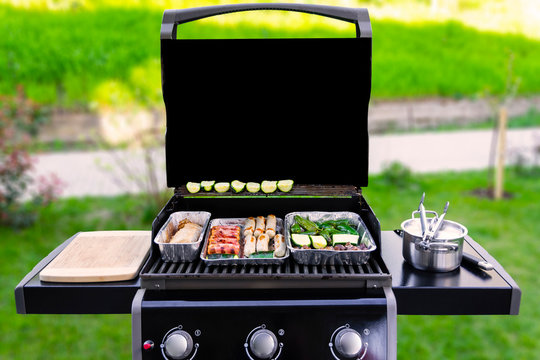 An opened gas grill with vegetables, meat, and sausages in aluminum barbeque trays or dip pans. The background with green grass, bushes, a sidewalk are blurred. copy space on the black grill cover.