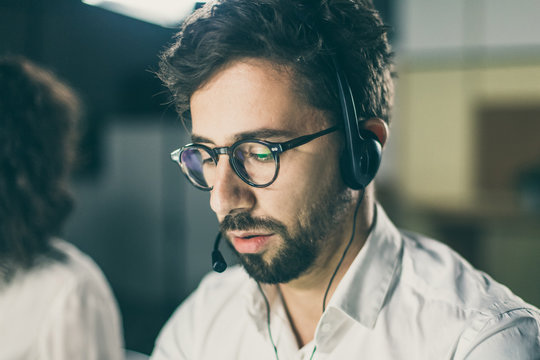 Closeup shot of confident call center operator. Handsome young man with headset looking down. Call center concept