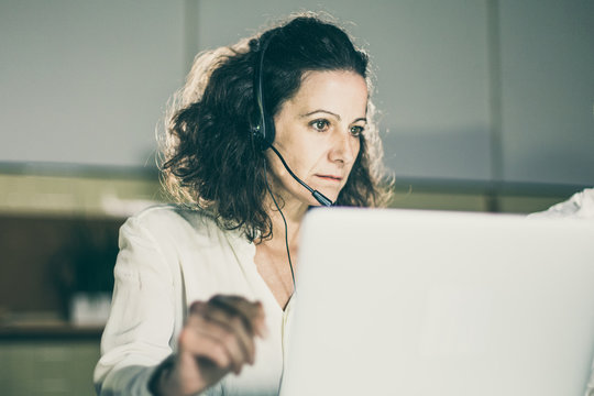 Focused mature call center operator looking at laptop. Serious curly woman working in office. Call center concept