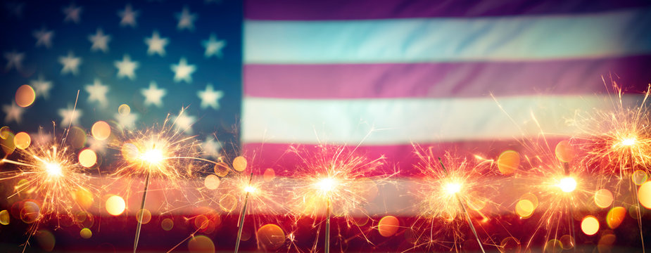 Usa Celebration With Sparklers And Blurred American Flag On Vintage Background