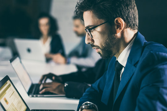 Serious businessman sitting at table and looking at laptop. Side view of focused man in eyeglasses working with laptop. Business, working late concept