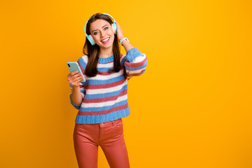 Portrait of her she nice attractive lovely cute cheerful cheery brown-haired girl holding in hands mp3 player listening stereo sound rock isolated on bright vivid shine vibrant yellow color background Wall mural
