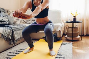 Home workout during coronavirus quarantine. Woman training using mat sport belt. Booty glutes building. Squates