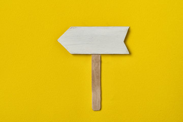 Wall Mural - Wooden arrow pointer on yellow background. Copy space, mock-up