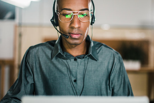 Concentrated call center operator talking with client. Front view of thoughtful call center operator during working process. Call center concept