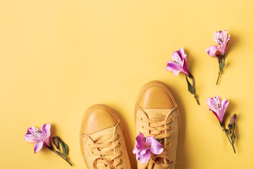 Pair of yellow sneakers and flower buds on yellow background. Spring summer fashion concept Fotobehang