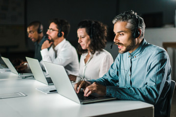 Focused call center operators during working process. Confident client support team at workplace. Call center concept