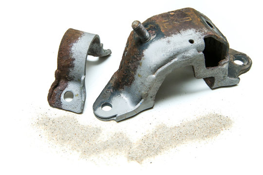 The overgrown rusty cast iron parts partly sand blasted together with sand isolated in a white background.