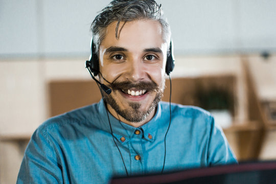 Smiling call center operator looking at camera. Handsome bearded man working with laptop in office. Call center concept