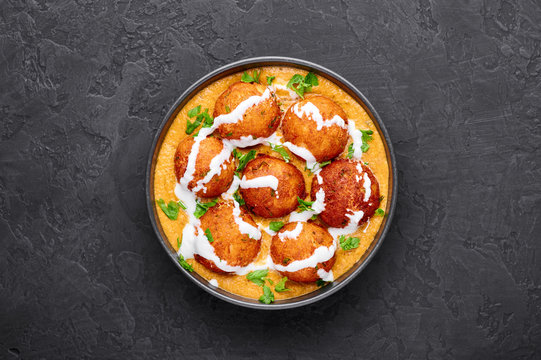 Malai Kofta Curry in black bowl at dark slate background. Malai Kofta is indian cuisine dish with potato and paneer cheese deep fried balls in onion tomato gravy with spices. Indian Food.
