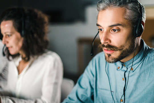 Handsome young man with headset looking at laptop screen. Confident bearded call center operator at workplace. Call center concept
